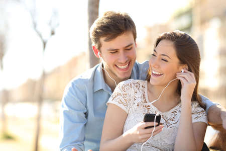 listening ear: Couple listening to the music with earbuds from a smart phone in a park with an urban background Stock Photo