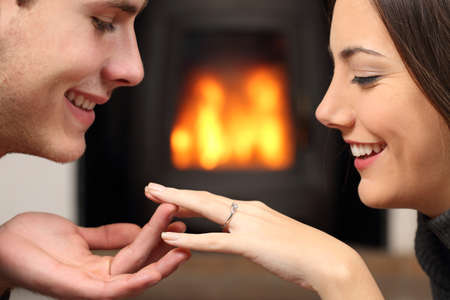 jewelry: Couple looking a engagement ring after proposal at home with a fire place in the background Stock Photo