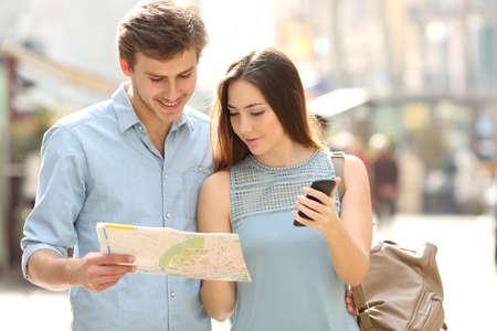 Coppia di turisti di consulenza una guida della città e gps telefono cellulare in una strada