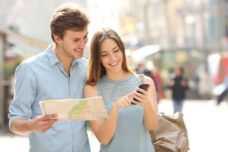 persona viajando: Pareja de turistas que consultan a un guía de la ciudad y de los gps de teléfonos inteligentes en los lugares de la calle a buscar Foto de archivo