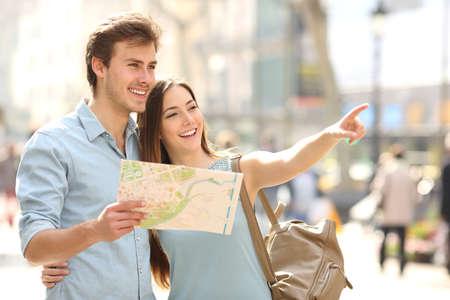 Casal de turistas consultar um guia da cidade a procurar locais na rua e apontando