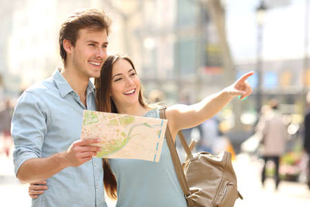 Para turystów skorzystali z przewodnika po mieście szukając miejsc w ulicy i wskazując Zdjęcie Seryjne