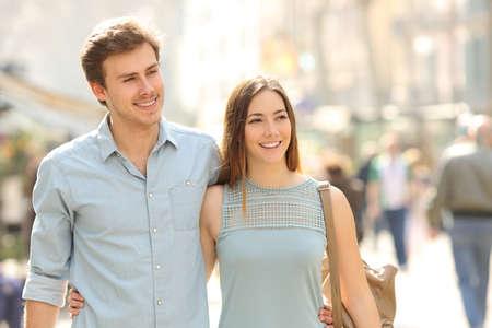 都市の通りの歩道で、晴れた日に散歩をして観光客のカップル