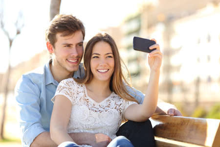 Couple photographing a selfie with a smart phone in a park with an urban background in a sunny day photo