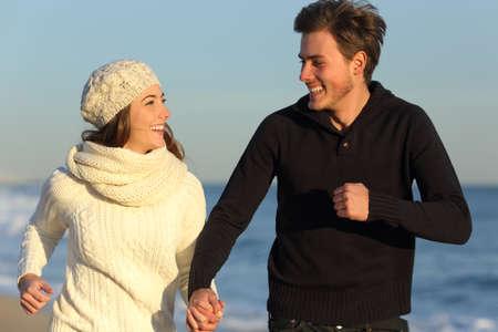 jovenes enamorados: Pareja feliz corriendo en la playa en invierno con el mar de fondo