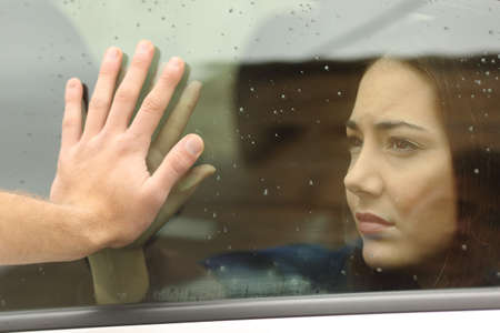relationship breakup: Couple saying goodbye before car travel holding hands through the window Stock Photo