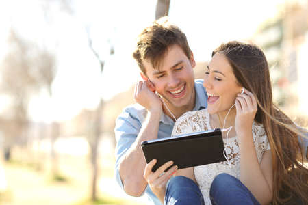 Couple sharing music and singing with a tablet sitting in a bench in an urban park Stock Photo