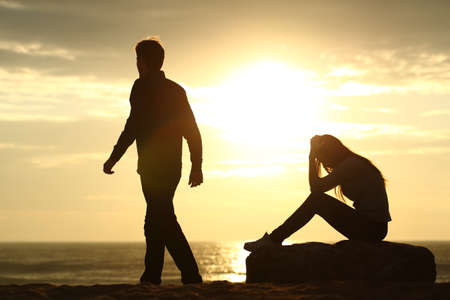 Couple silhouette breaking up a relation on the beach at sunset Foto de archivo