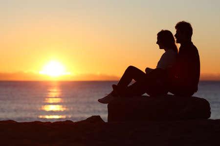 femme romantique: Vue latérale d'un couple assis à regarder silhouette soleil au coucher du soleil sur la plage