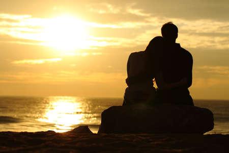 Silhouet van het paar knuffelen en kijken naar de zon bij zonsondergang op het strand