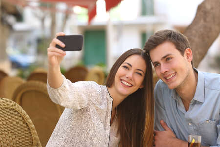 Happy couple taking a selfie photo with a smart phone in a restaurant terrace photo