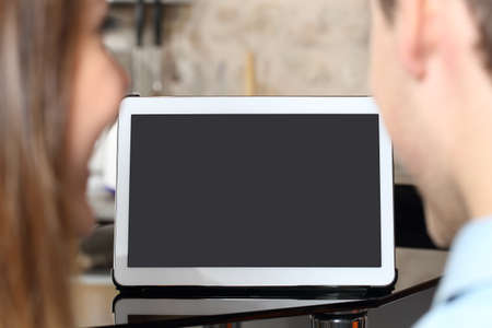 looking at viewer: Couple watching and showing a blank tablet screen at home