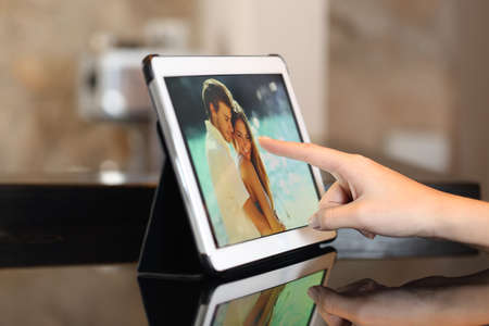 Woman hand using a tablet watching photos and touching screen at home Stock Photo