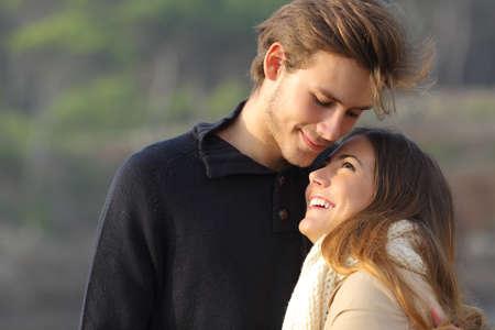 pareja abrazada: Abrazos pareja feliz en el amor al aire libre en la puesta del sol con un fondo desenfocado