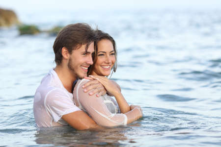 first love: Happy couple in love hugging and bathing on the beach and looking away