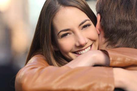 행복한 여자 친구의 초상화는 그녀의 남자 친구를 포옹 카메라를 찾고