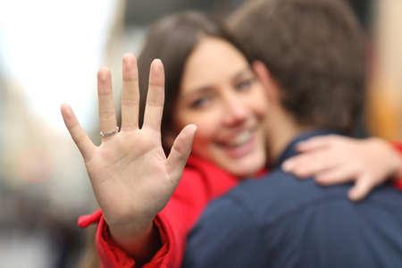 matrimonio feliz: Mujer feliz mirando anillo de compromiso después de la propuesta, mientras que está abrazando a su novio en la calle