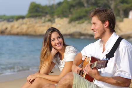 guitarists: Man flirting playing guitar while a girl looks him amazed with the sea in the background