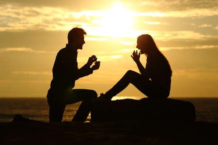 anillo de compromiso: Propuesta en la playa con una silueta hombre que pide casarse al atardecer con el sol en el fondo