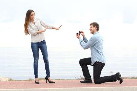matrimonio feliz: Propuesta de rechazo cuando un hombre feliz pide en matrimonio a una mujer en la playa Foto de archivo