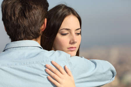 persona triste: Triste mujer abrazando a su novio y mirando hacia abajo problemas de pareja concepto Foto de archivo