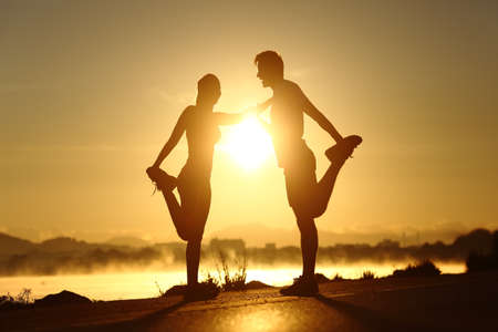 Silhouette of a fitness couple profile stretching at sunset with the sun in the background
