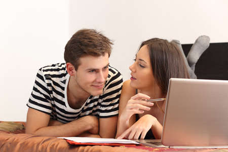 Students studying and learning at home with a laptop and notes photo