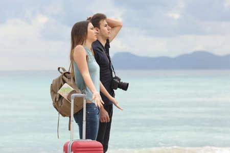 観光客、悪いとイライラするとき天気曇り空を背景とビーチに到着