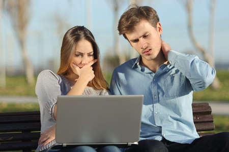 Worried students or entrepreneurs watching a laptop sitting on a bench in a park