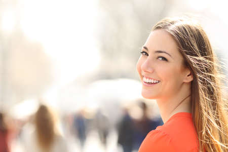 Beauty vrouw met perfecte glimlach en witte tanden lopen op de straat en kijken naar de camera