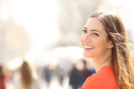 Krása ženy s dokonalým úsměvem a bílé zuby chůzi na ulici a díval se na kameru