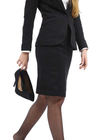 Business woman walking holding heels in her hand isolated on a white background