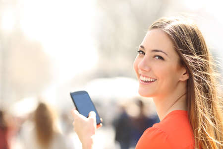 device: Happy woman smiling and walking in the street using a smartphone and looking at camera Stock Photo