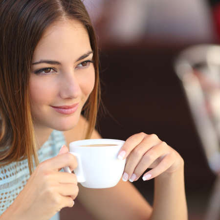 Pensive woman tasting coffee in a restaurant holding a cup with an unfocused background