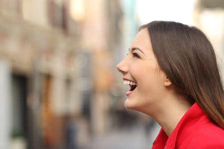 profil: Profil twarzy kobiety śmiechu szczęśliwy na ulicy z rozmytą tle miejskiego