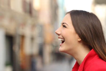 laughs: Profile of a woman face laughing happy in the street with an unfocused urban background