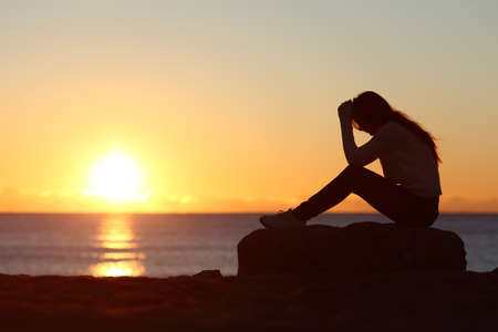 Sad woman silhouette worried on the beach at sunset with the sun in the background Stockfoto