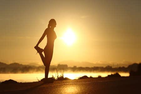 Silhouet van een fitness vrouw profiel uitrekken zich bij zonsopgang met de zon op de achtergrond Stockfoto