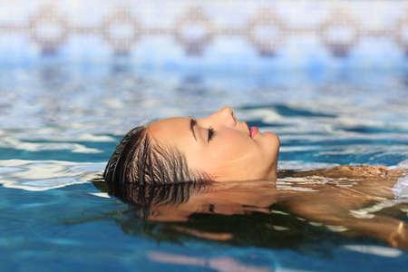 Vista lateral de un rostro de mujer relajante flotando en el agua de una piscina o spa Foto de archivo