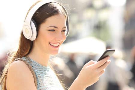 Vrouw luisteren draadloos muziek met een hoofdtelefoon van een slimme telefoon in de straat Stockfoto