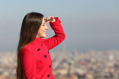 mujer mirando el horizonte: Mujer que mira adelante en invierno con un abrigo rojo con la ciudad en el fondo Foto de archivo