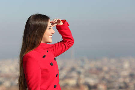 scouts: Woman looking forward in winter with a red coat with city in the background
