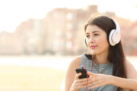 listening device: Candid girl thoughtful and listening to the music with a smart phone and looking away