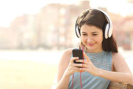 Girl listening music with headphones from a smart phone sitting in a bench in a park