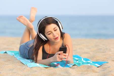 listening device: Teen girl listening to the music from a smart phone and singing lying on the sand of the beach Stock Photo