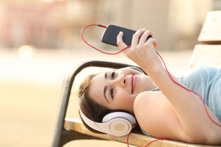 listening device: Teen girl listening to the music from a smart phone lying in a bench of a park Stock Photo