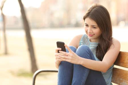 adolescente: Muchacha adolescente que usa un tel�fono inteligente y mensajes de texto que se sienta en un banco de un parque urbano