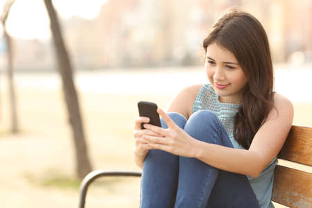Teen girl using a smart phone and texting sitting in a bench of an urban park Imagens - 37931619