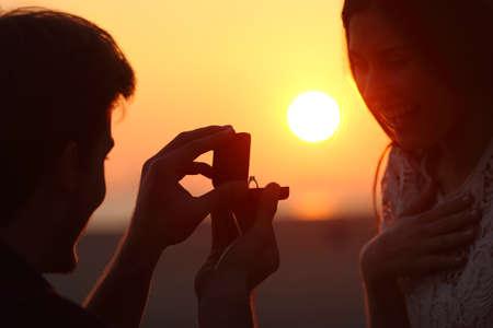 夕暮れ時のビーチで結婚のカップルの提案のバックライト 写真素材