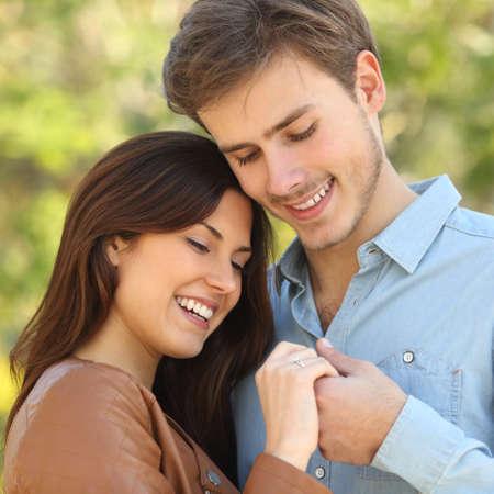 verlobung: Paar umarmt und H�ndchen haltend w�hrend sieht einen Verlobungsring im Freien Lizenzfreie Bilder